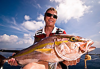 Maldives Islands November 2008, Indian Ocean. Caucasian fisherman in his 40s holding an Amberjack (Seriola rivoliana), a member of the carangide family found in all temperate waters. Shot taken at the