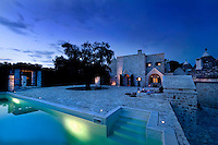 The illuminated swimming pool and terrace at dusk, an ideal place to relax on a summer evening