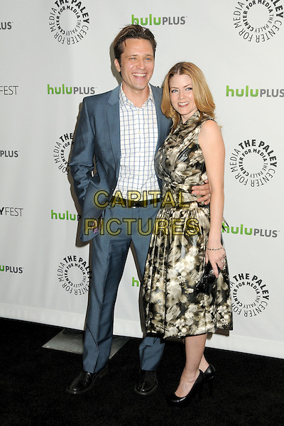"Seamus Dever, Juliana Dever.PaleyFest 2012 Presents ""Castle"" held at The Saban Theatre, Beverly Hills, California, USA, 9th March 2012..full length blue jacket white checked shirt print dress  grey gray print suit belt black arm around .CAP/ADM/BP.©Byron Purvis/AdMedia/Capital Pictures."