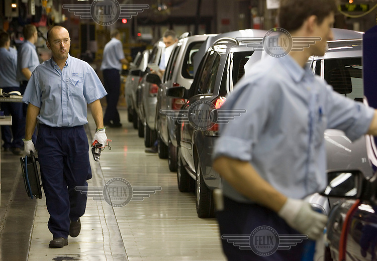 Factory workers help to assemble cars on a production line at the General Motors (GM) car manufacturing plant.