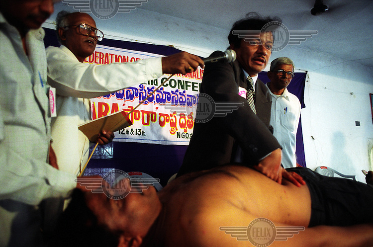A public display by Mr Vikram at the 2nd annual conference of India's Federation of Atheist, Rationalist and Humanist Associations. Mr Vikram seeks to debunk myths and to prove that the so-called miracles performed by fake gurus are just tricks. Here he mimics the holy men's 'spiritual surgery', removing a tumour which he later reveals to be a piece of chicken gizzard. But the rationalists have a tough task on their hands in a subcontinent often hobbled by superstition.