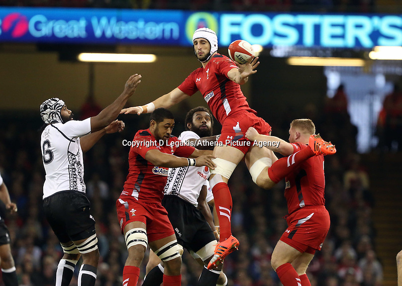 Pictured: Luke Charteris of Wales (C) clumsily passes the ball after a line out. Saturday 15 November 2014<br /> Re: Dove Men Series rugby, Wales v Fiji at the Millennium Stadium, Cardiff, south Wales, UK.