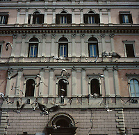 Birds fly over a building facade in Rome, Italy in the summer of 2007.