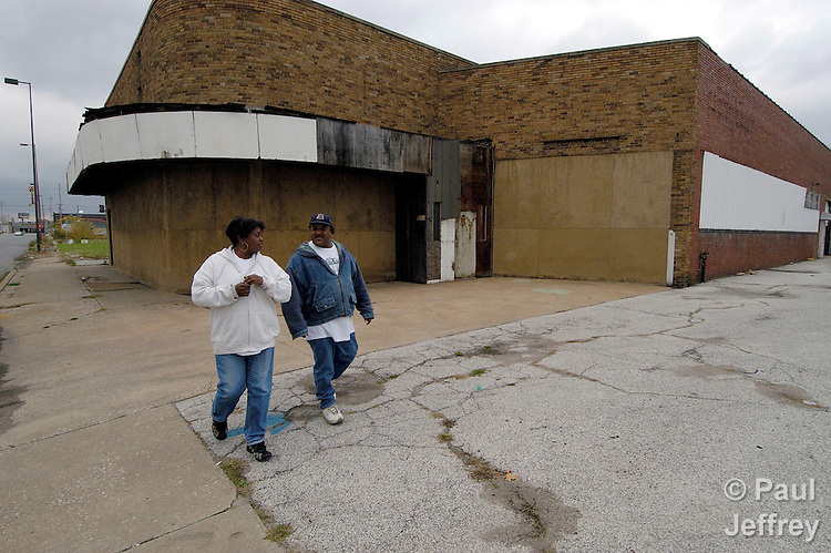 Herb Lester and Gloria Walton walk past a shuttered building in East St. Louis, Illinois.