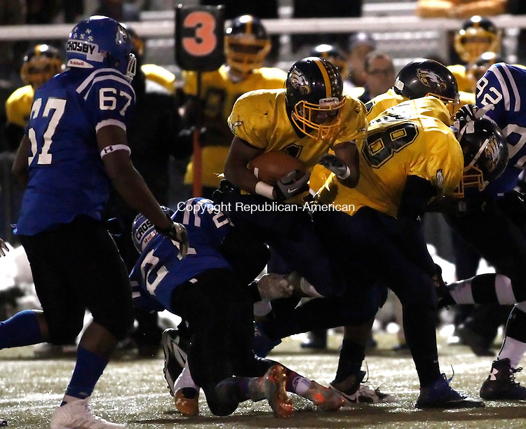 Waterbury, CT- 28 November 2014-112814CM08-  Kennedy's Stanley Little carries the ball as Crosby's Josiah Martinez tries to bring him down in Waterbury on Friday.  Also in the play is Crosby's Joe Potter (67).  Kennedy won, 55-20. Christopher Massa Republican-American
