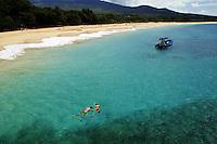 Snorkeling couple (MR) enjoying Hawaii's tropical fish and reefs and a charter boat off Makena Beach, Maui, Hawaii.