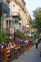 People sitting and talking in outdoor restaurants and bistros on Rue Saint Denis street, Latin Quarter, Montreal, Quebec, Canada