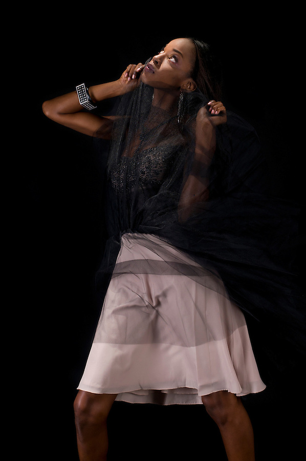 African American woman model posing with dress in black background.