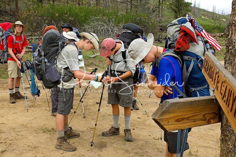 Photo story of Philmont Scout Ranch in Cimarron, New Mexico, taken during a Boy Scout Troop backpack trip in the summer of 2013. Photo is part of a comprehensive picture package which shows in-depth photography of a BSA Ventures crew on a trek.  In this photo BSA Venture Crew Scouts work together to review the  map as they confirm their trail direction choice in the backcountry at Philmont Scout Ranch.   <br /> <br /> The  Photo by travel photograph: PatrickschneiderPhoto.com