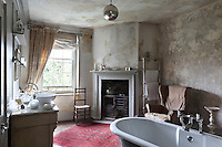 A freestanding roll top bath placed in the centre of a period bathroom. A cast iron stove stands in a fireplace recess and the walls and ceiling have a distressed finish effect.