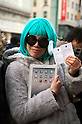 March 16, 2012, Tokyo, Japan - A Japanese woman carries his iPad 2 and shows her tickets reservation, the papers shows the model, color and type of iPad that it will buy. Fans lined up overnight outside the Apple store in Ginza, to buy the new iPad. Japan was one of the first countries where Apple fans could get their hands on the new iPad.