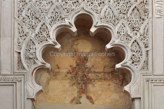 Decorative plasterwork from the West Wall of the prayer room of the Cordoba Synagogue, built 1315 in Mudejar style by architects including Isaac Moheb, in the Jewish quarter of Cordoba, Andalusia, Southern Spain. This detail shows a polylobal arch surrounded by intricately carved plasterwork, with a cross painted on the wall in the niche. The historic centre of Cordoba is listed as a UNESCO World Heritage Site. Picture by Manuel Cohen
