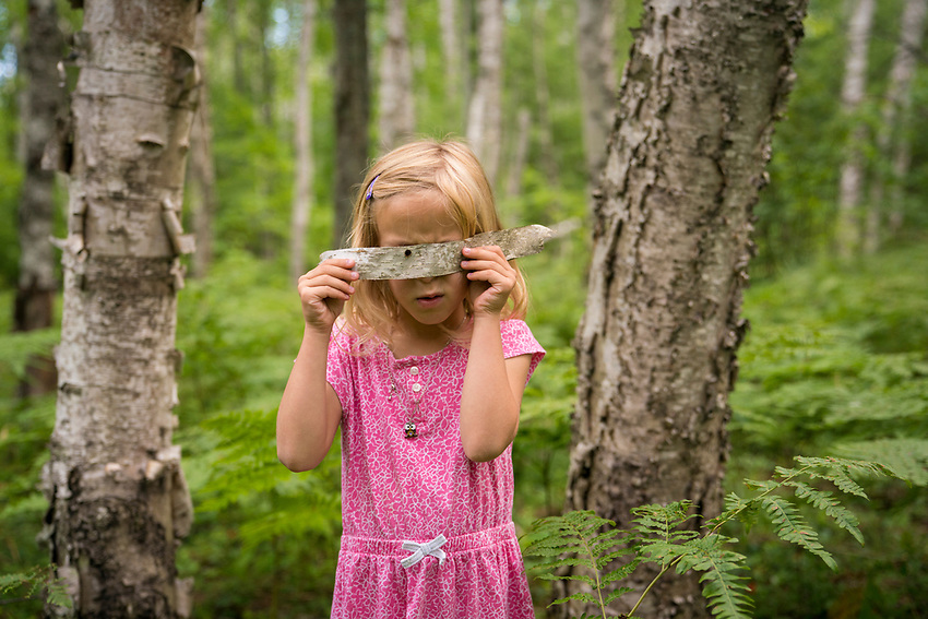 A young girl peeks through a hole in a scrap of white birch bark while hiking at Pictured Rocks National Lakeshore in Michigan.