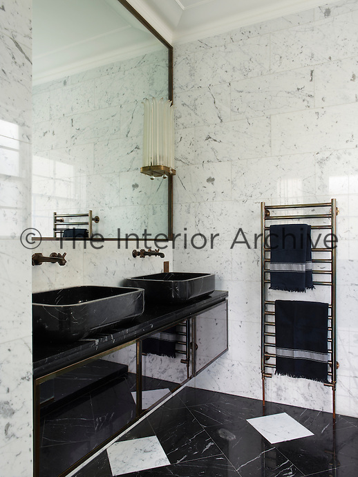 The ensuite master bathroom is sheathed in Nero Marquina black and white marble. The twin washbasins sit on a glossy storage unit placed beneath a large mirror.