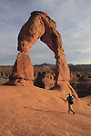Man hiking under Delicate Arch in Arches National Park, Moab, Utah, USA. .  John offers private photo tours in Arches National Park and throughout Utah and Colorado. Year-round.