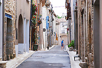 Village street with an old man walking across the street. St Jean de Fos village. Languedoc. France. Europe.