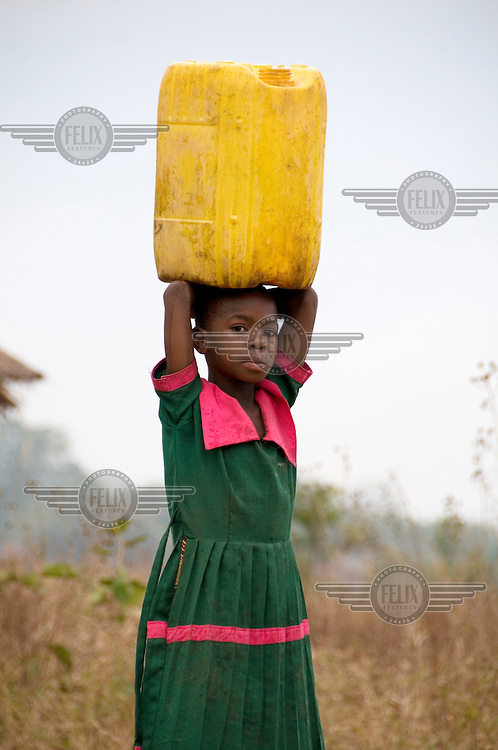 Maria carries a bucket of water on her head near her home in Sambo village.