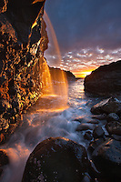 Sunset illuminates the waterfall as it hits the ocean in Princeville, Kauai.