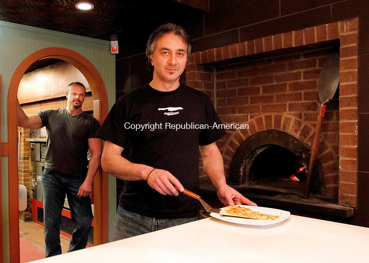 Middlebury, CT-29 December 2011-122911CM03-  Theofilos Anastasiadis (front) and Christos Gogas, co-owners of Pies and Pints Pizzeria and Pub of Middlebury pose in their newly renovated restaurant in Middlebury Thursday afternoon.  The restaurant, formerly Perrotti's West Street Pizza and Pub will feature a new menu in 2012.   Christopher Massa Republican-American