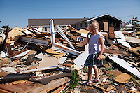 Jada Smith stands on the rubble of her former home on Aug. 27, 2011 in Joplin, Mo. Susan Bragole, Jada Smith's grandmother, took her grandchildren to see the house for the first time since the tornado. When the tornado hit, Smith was in the bathtub calming her mother while Bragole laid on top of them to protect them.