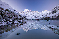 Aoraki Mt Cook & the Southern Alps reflected in Hooker Lake, twilight alpenglow.  Aoraki Mt Cook National Park, NZ.