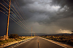 Storm clouds over a road in America with telephone poles stretching into the distance
