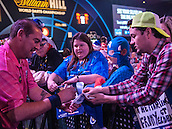21.12.2014.  London, England.  William Hill World Darts Championship.  Dean Winstanley (26) [ENG] signs autographs for fans after his win over Wayne Jones [ENG].
