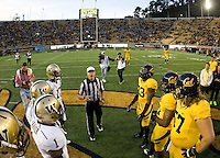 California and Washington captains watch referee Shawn Hochuli toss the coin before the game at Memorial Stadium in Berkeley, California on November 2nd, 2012.  Washington Huskies defeated California, 13-21.