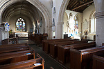 View past wooden pews through chancel arch to sanctuary and altar inside the church at Urchfont, Wiltshire, England, UK also showing side chapel in south aisle