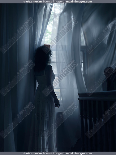 Young woman in a white dress standing by a window with flying in the wind curtains in a dark room of a house in dim dramatic light