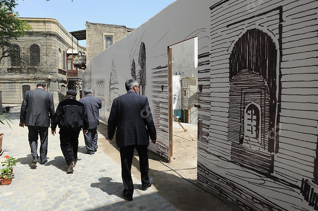 A man walked past a construction site in the old town of Baku, a UNESCO site, which has been almost entirely restored. Azerbaijan, May 14, 2011