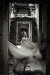 A young woman dances through dark interior passages of an ancient temple