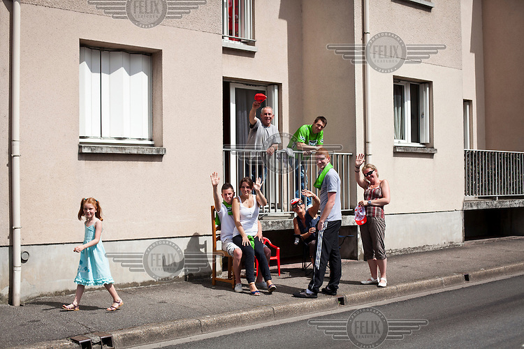 Local people outside a house on the side of a street as they wait see the Tour de France cycling competition pass through their village.