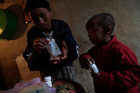 Tlbech, 27 years old, and her son Zarhiun, 4, both HIV positive prepare their medications in their small house in one of the poorest neighborhoods in Addis Ababa, ethiopia on Friday July 28 2006..Talbech and Zarihun live on a 180 birr ( 20 USD ) per month sponsorship from the HfC NGO. they spend 100 Birr for rent leaving less than 10 USD for food and other necessities. Nevertheless they are a privileged family in the country..Tlbech besides fighting againt the virus and taking care of her child provides home base care assistance in Addis to other HIV patients in need..Ethiopia is one of the countries most affected by HIV/AIDS. Of its population of 77 million, three million are HIV-positive, according to government statistics. Every day sees 1,000 new infections. A million children under 14 have lost one or both parents to AIDS, and 200,000 children are living with AIDS. That makes Ethiopia the country with the most HIV-positive children.
