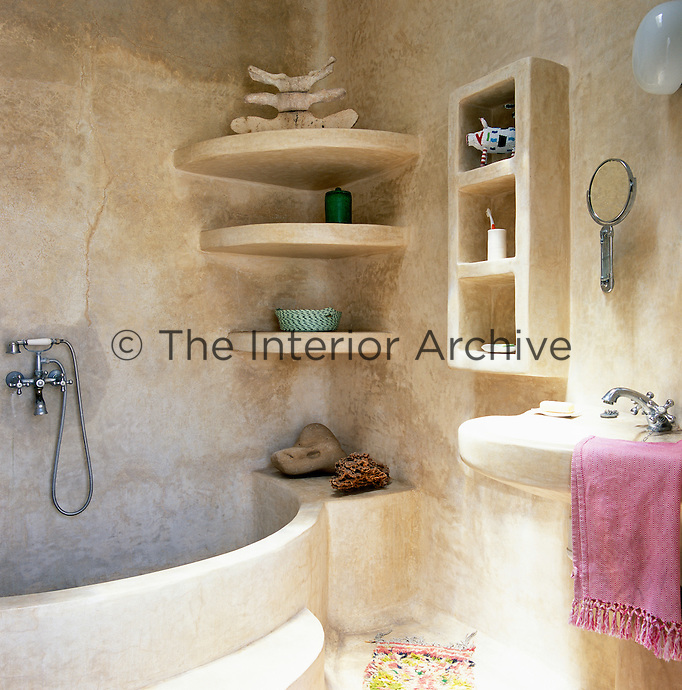 The shelving, bath and basin in this traditional Moroccan tadelakt bathroom are built-in and organic in shape