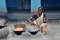 Monika Besra (42) during her daily chore at her house at Danagram a village 40 kms away from Malda Town,  West Bengal, India. 20th August 2010.  Monica Besra says that her non curable tumour got cured on the first annivarsary of Mother Teresa's death by putting a Mother Teressa Medellion on the swollen part of her abdomen, which was recognized by the Vatican in the year 2002 and started the process of Mother Teresa's beatification, a major step towards sainthood.