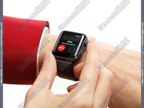 Woman hand with Apple Watch smartwatch on her wrist displaying incoming phone call isolated on white background