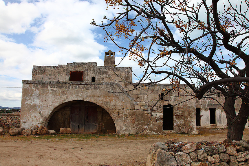 Near the remains of the ancient Egnazia (Fasano), a beautiful old house in the countryside. In the photo. its frontal part is in foreground, with a suggestive tree on the right, under a partially clouded sky. Digitally Improved Photo.
