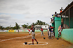 Players await their turn at bat during a baseball game between the Warriors and Indian Rocks on Friday, February 26, 2010 in San Antonio de Guerra, Dominican Republic.