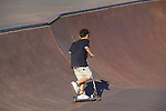 Boy riding his scooter in a skateboard park in Denver, Colorado. .  John offers private photo tours in Denver, Boulder and throughout Colorado. Year-round.