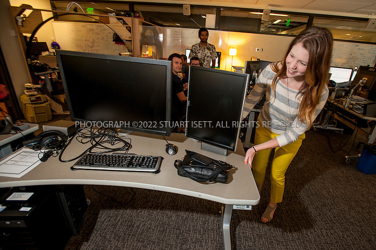 8/2/2012--Bellevue, WA, USA..Emily Kent moves a desk into an office for a new employee joining gaming software maker Valve...The office is set up as a 'boss less' office that is fluid and non-hierarchical. Desks come with wheels so that they can be easily moved and reconfigured to create new work spaces for new projects. The desks can also be raised or lowered for comfort or to create a standing work space...©2012 Stuart Isett. All rights reserved.