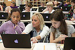 November 15, 2011. Mooresville, NC.. Mrs. Rigby, a 5th grade science teacher at East Mooresville Intermediate School, helps Grace Lateef, left, and Caitlyn Yaede with an in class exercise. Many of the in-class lessons are done on school issued laptops and turned in to the teacher via networked printer.. The Mooresville school system has become nationally known for being on the cutting edge of using technology as an educational tool. Starting in 3rd grade, each student is issued their own laptop that they will use in class and at home to further their learning.