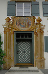 Mural painted on wall showing ornate artwork tromp l'oeil around and above the door. Oberammergau, Bavaria, Germany.