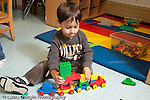 Education preschool 3-4 year olds boy putting together Duplo train sticking his tongue out with effort horizontal