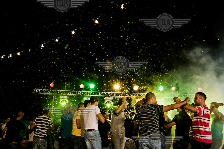 Men dance and sing at a party hosted by a wealthy Ramallah family on the outskirts of the city.