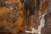 A hiker observes the colorful canyon walls of Willis Creek in Southern Utah's Grand Staircase Escalante National Monument