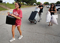 NWA Democrat-Gazette/DAVID GOTTSCHALK Christina Trexler (from left), of Springdale, carries items with her parents Greg Misenheimer and Sandy to her dorm room Thursday, August 9, 2018, on the first day of Move-in for the 2018-2019 school year on the campus of the University of Arkansas in Fayetteville. University Housing coordinates the effort and staff expect more than 5,200 students to be moving into residence halls during this period.