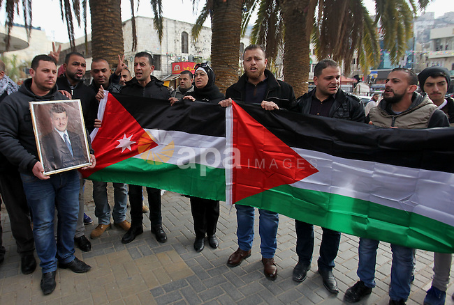 Palestinians take part during a protest to show solidarity with Jordan against terrorist attacks in the West Bank city of Nablus, on December 21, 2016. Jordanian security forces have arrested a man suspected of funding an attack by the Islamic State group that killed 10 people including a Canadian tourist, a security source said. The suspect was detained in a raid on a house in Karak province on Tuesday by police looking for the perpetrators behind Sunday's shooting spree. Photo by Nedal Eshtayah