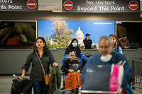 Passengers arrive from Dubai after a 14-hour flight on Emirates flight 231, at the international terminal at Dulles International Airport in Dulles, Va., Monday, March16, 2020. Some people are taking the precaution of wearing face masks as they arrive to be greeted by family and or friends. Credit: Rod Lamkey / CNP/AdMedia