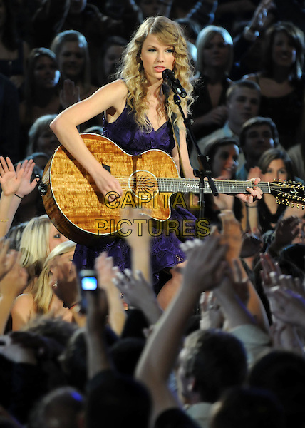 TAYLOR SWIFT .performs during the 43rd Annual CMA Awards, Country Music's Biggest Night, held at the Sommet Center, Nashville, Tennessee, USA, 11th November 2009. live show on stage half length performing concert music gig guitar crowd audience purple microphone singing playing .CAP/ADM/LF.©Laura Farr/AdMedia/Capital Pictures.